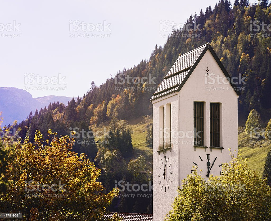Swiss village clock tower with Autumn treetops royalty-free stock photo