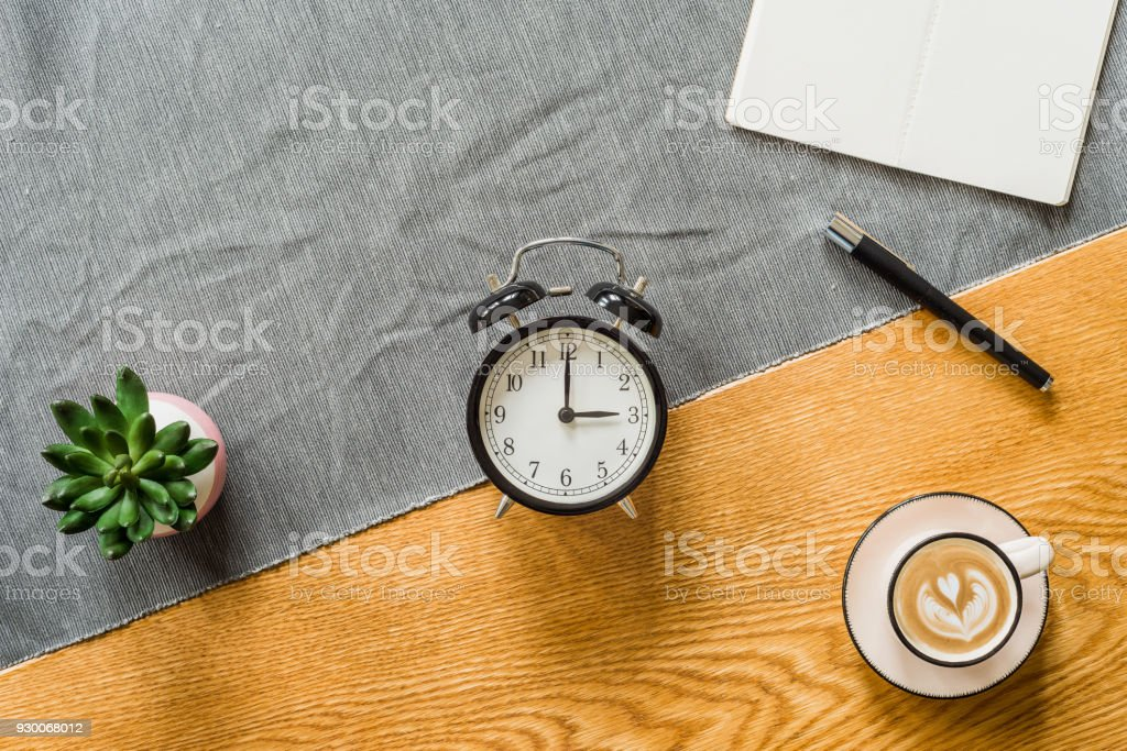 Switch to summer time on alarm clock with copyspace on notebook from above stock photo