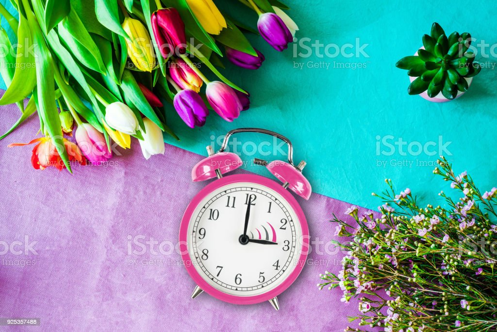 Switch to summer time on alarm clock with tulips and flowers from above stock photo