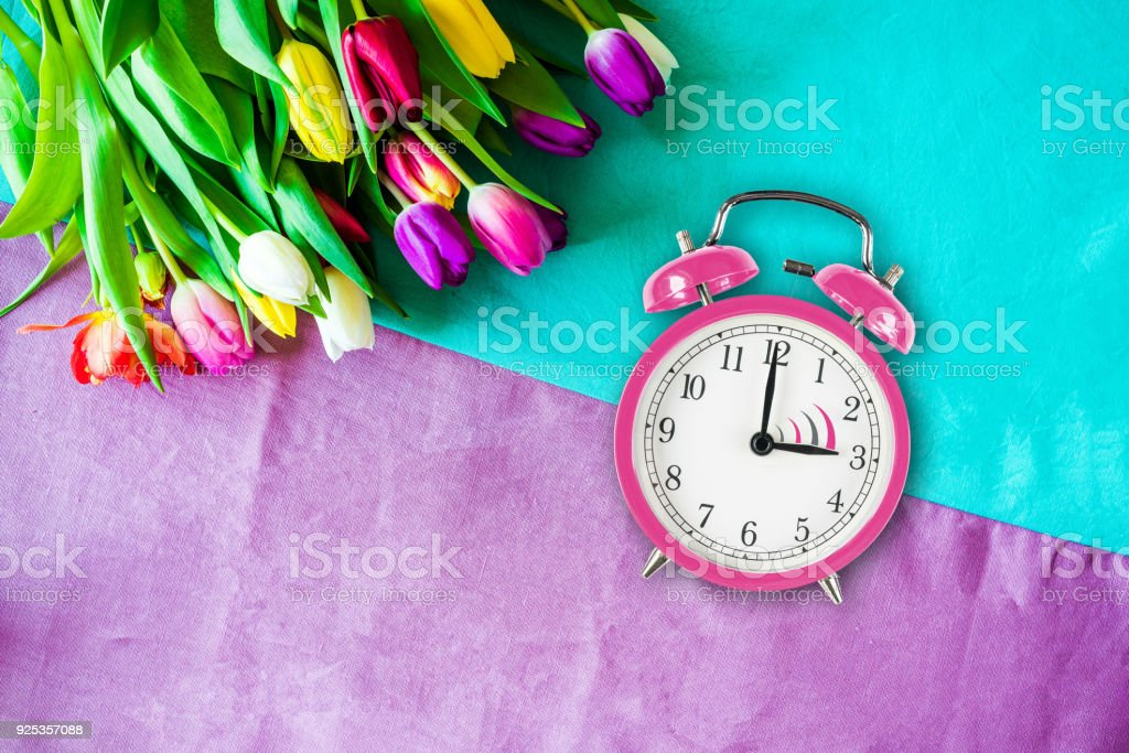 Switch to summer time on alarm clock with tulips from above stock photo