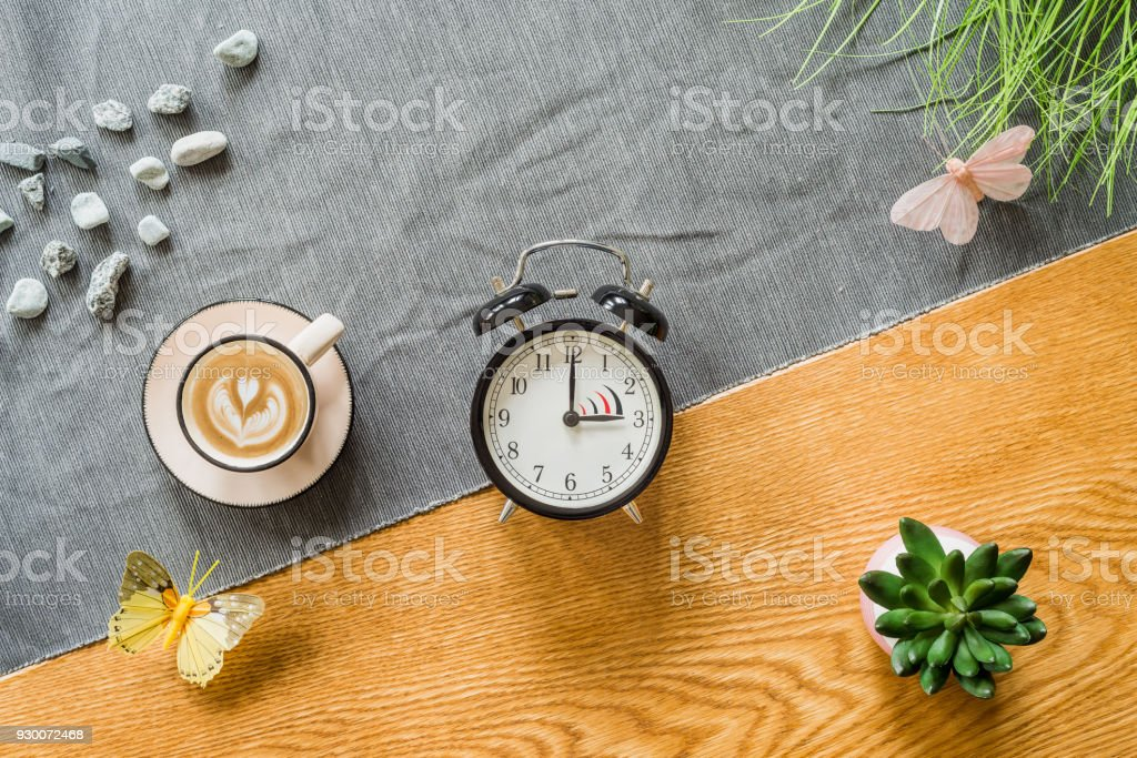 Switch to summer time on alarm clock with wooden background from above stock photo