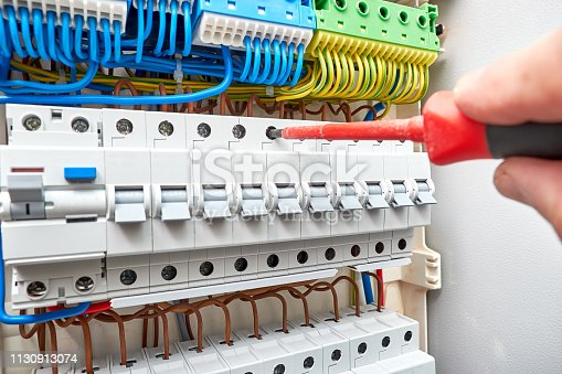 istock Switchboard with automatic circuit breakers. Dielectric screwdriver in the electrician hand. 1130913074