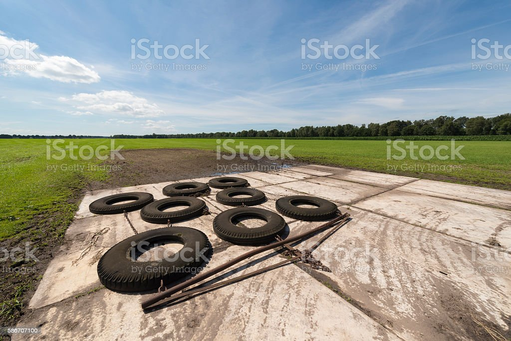 Switched tires to level out bumpy agricultural field. stock photo