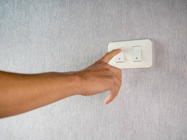 Switching on off light switcher on wall stock photo