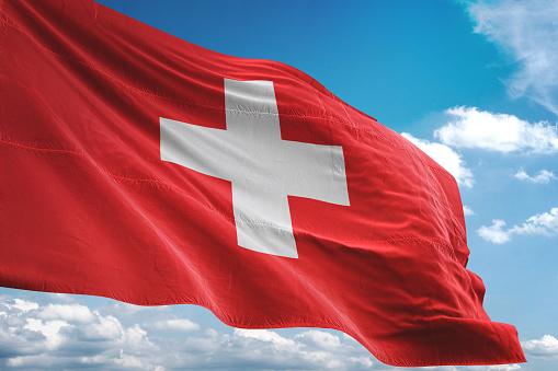 Switzerland flag waving cloudy sky background