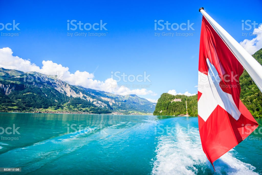 Switzerland National Flag at cruise boat's rear end with beautiful summer view of Swiss natural alps, lake and clear blue sky as a background, Lake Brienz, Interlaken-Oberhasil, Bern, Switzerland. stock photo