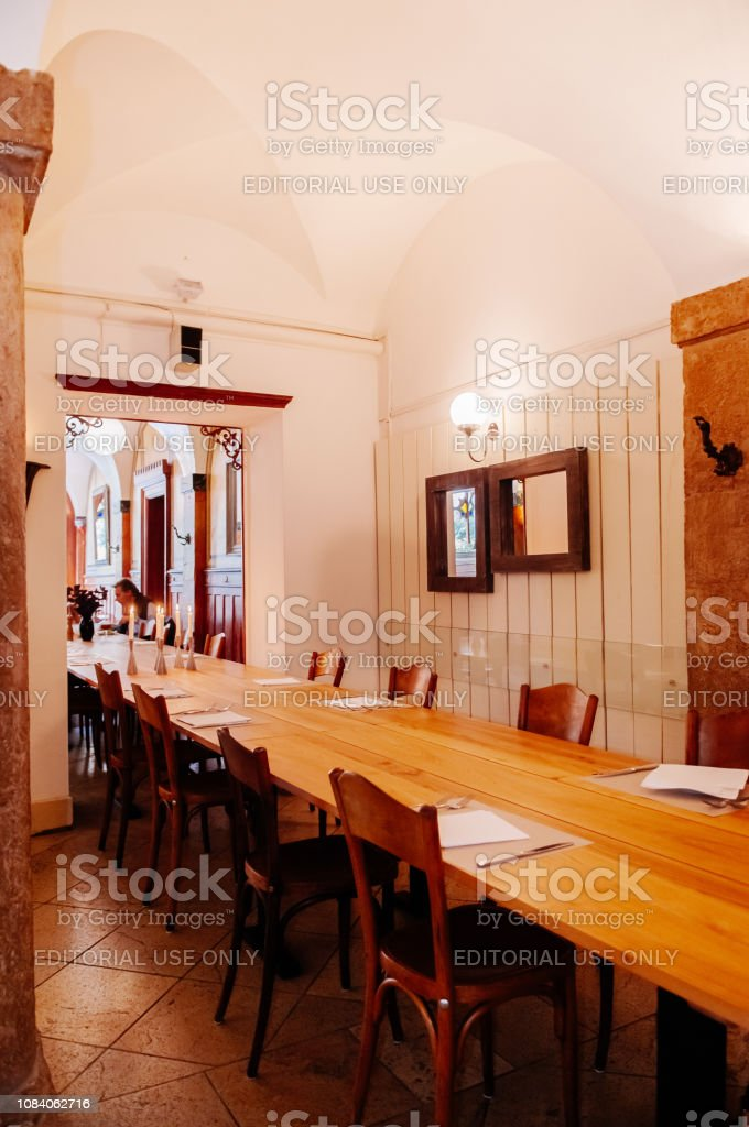 Switzerland - Old vintage restaurant with wooden long table under arch ceiling and warm tone light in La Chaux de Fonds stock photo