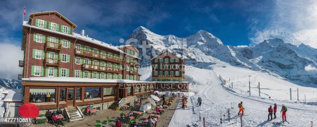 Kleine Scheidegg, Switzerland - 27th February 2014: Skiers enjoying the bright winter sunshine at the famous Kleine Scheidegg Bellevue des Alpes hotel resort overlooked by the iconic north face of the Eiger and the snow capped peaks of the Monch and Jungfrau high in the Bernese Alps, Switzerland. Composite panoramic image created from nine contemporaneous sequential photographs.
