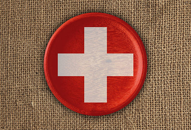 switzerland textured round flag wood on rough cloth - cruz roja fotografías e imágenes de stock