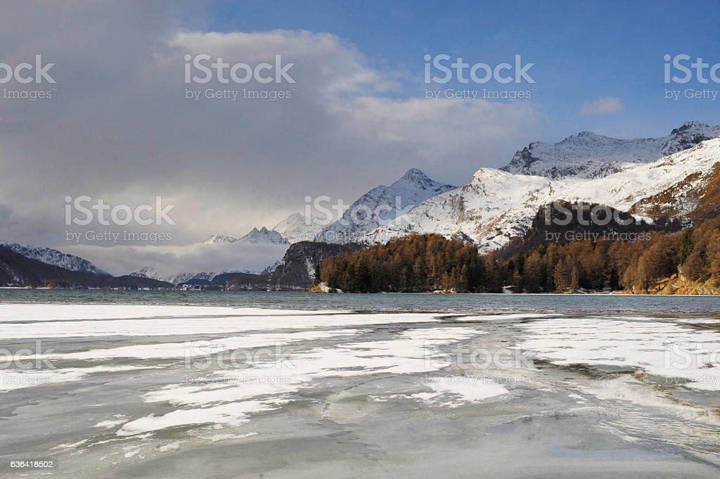 Switzerland village with snow on Alp mountains and frozen lake stock photo