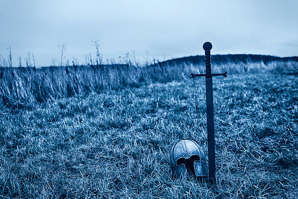 Sword and helmet symbols grave of warrior Sword is placed in the ground. Helmet by the side. battlefield stock pictures, royalty-free photos & images