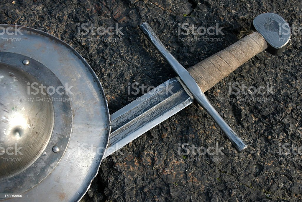 Sword and shield laying on the ground royalty-free stock photo