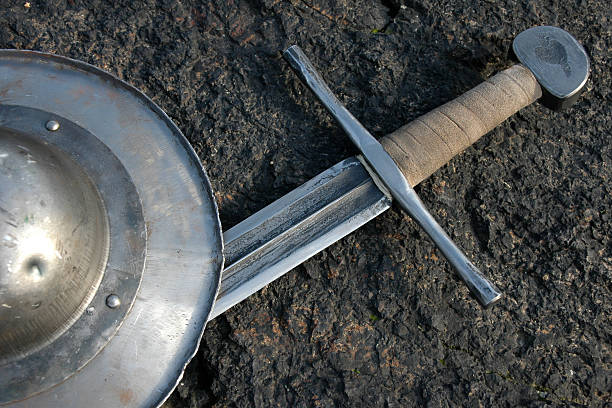 Sword and shield laying on the ground stock photo