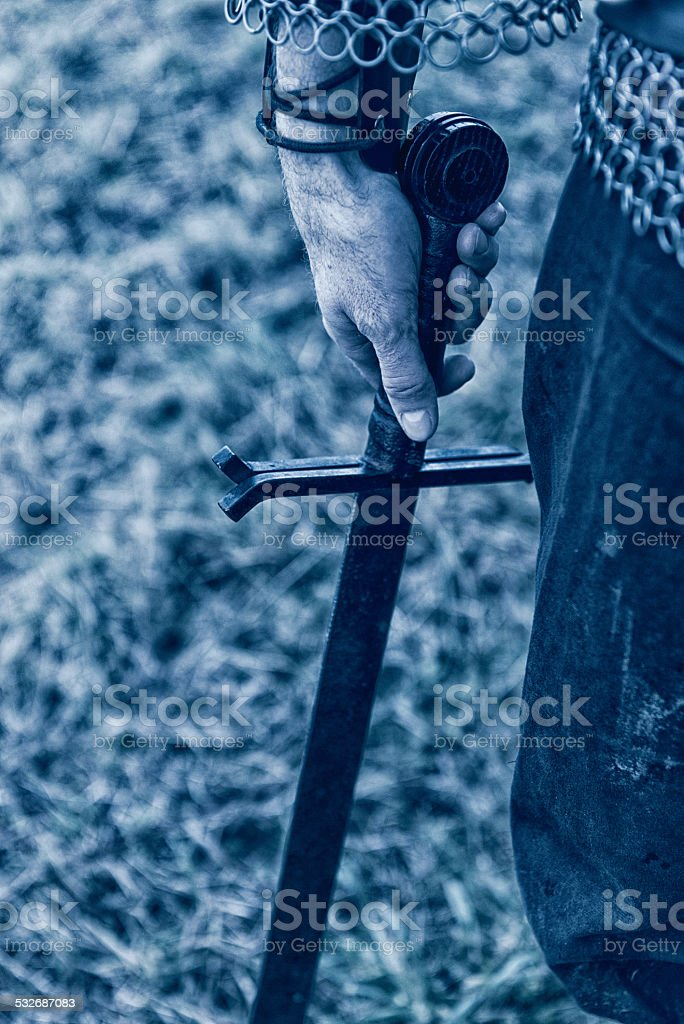 Sword in the hand of a warrior stock photo