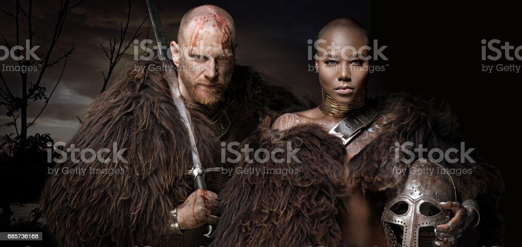 Sword wielding bloody viking soldier with warrior queen stock photo