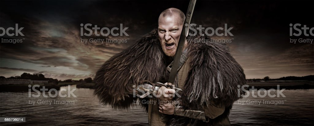 Sword wielding bloody viking warrior in studio shot stock photo