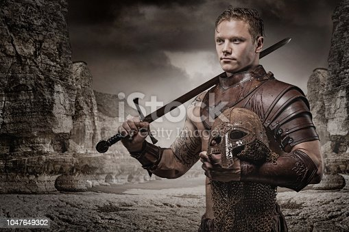Sword wielding bloody viking warrior in emotional pose in front of mountainous backdrop