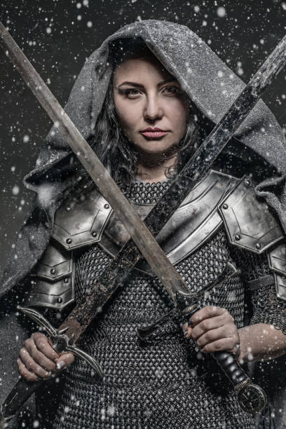 sword wielding viking warrior brunette female in studio shot - indumento corazzato foto e immagini stock