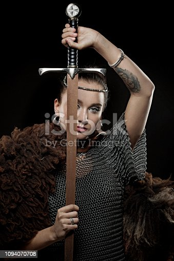 Sword wielding viking warrior young blond female in studio shot