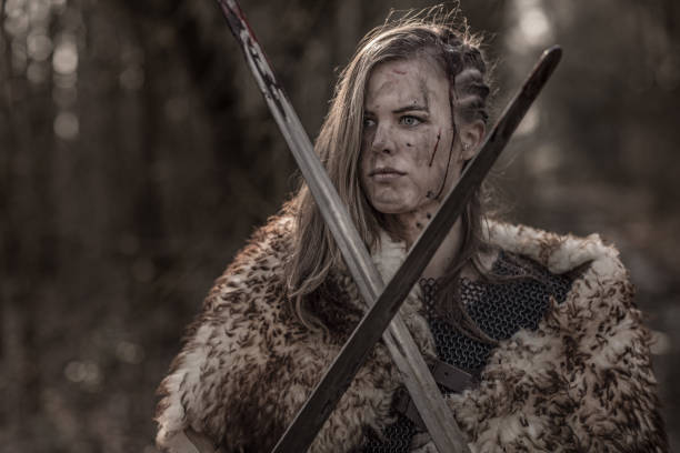 sword wielding viking warrior young blond female in wild highland countryside - indumento corazzato foto e immagini stock