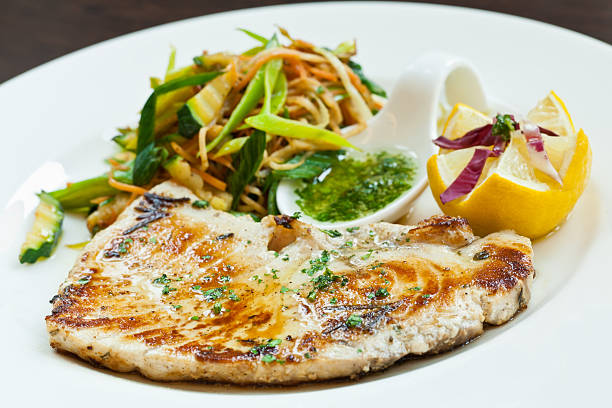 A swordfish filet with steamed vegetables and spices stock photo