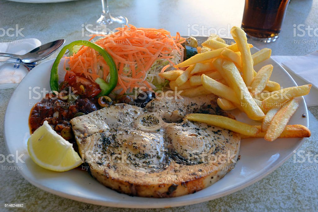 Swordfish in caper sauce with salad and French fries. stock photo