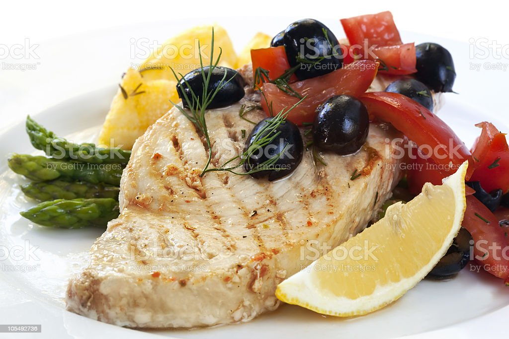 Swordfish played with asparagus, tomatoes, olives and lemons royalty-free stock photo
