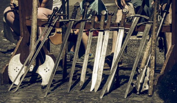 Swords set up in a row for the knight demonstration at a medieval market stock photo