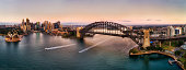 Major landmarks of Sydney city around Harbour on both sides of waterfronts connected by the Sydney Harbour bridge in wide aerial panorama at sunrise.