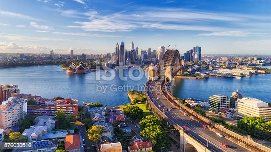 Cahill express way to the Sydney Harbour bridge across Sydney harbour towards city CBD landmarks in aerial eleveated wide view under blue morning sky.