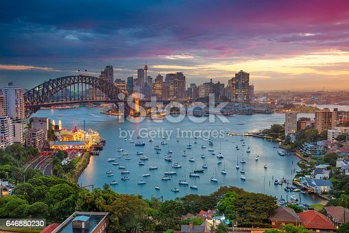 Cityscape image of Sydney, Australia with Harbour Bridge and Sydney skyline during sunset.