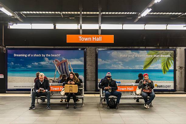 Sydney Town Hall Railway Station, Australia Sydney, Australia - June 1, 2015: Sydney Town Hall Railway Station platform, Australia on a winter's day. Passengers wait on benches. Three young people on smartphones face the camera as does one senior man who reads a newspaper. Other commuters face the railway track and two large sunsuper advertising panels featuring tropical beach scenes. subway platform stock pictures, royalty-free photos & images