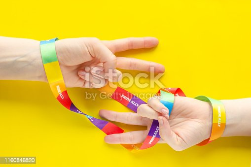 istock LGBT symbol diversity and inclusion - two hands wrapped in rainbow ribbon show V - symbol of victory 1160846820
