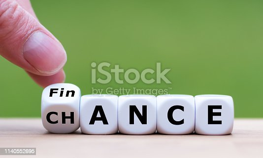 Symbol for a good finance chance. Hand turns a dice and changes the word