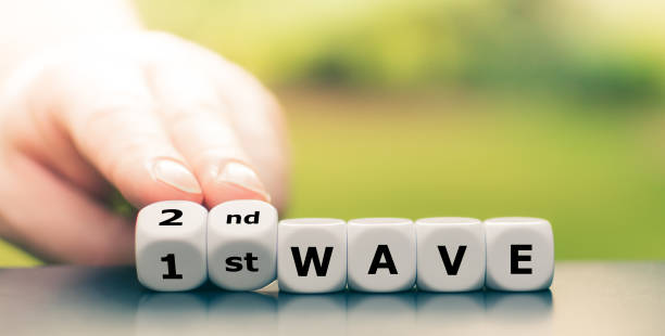 """Symbol for a second wave of the corona virus. Hand turns dice and changes the expression """"1st wave"""" to """"2nd wave"""" stock photo"""