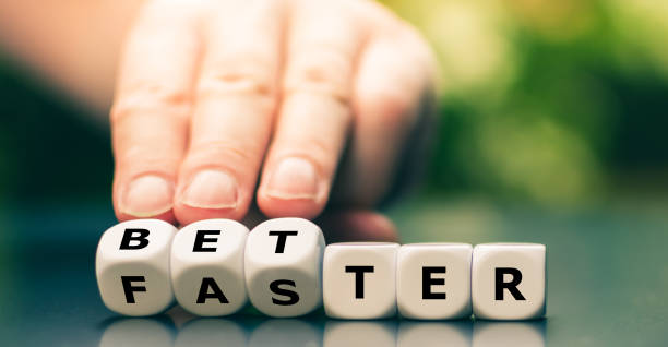 """Symbol for better work instead of faster work. Hand turns dice and changes the word """"faster"""" to """"better"""". stock photo"""