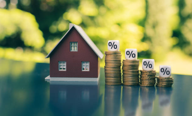 Symbol for decreasing interest rates. Dice with percentage symbols on decreasing high stacks of coins next to a model house. Symbol for decreasing interest rates. Dice with percentage symbols on decreasing high stacks of coins next to a model house. interest rate stock pictures, royalty-free photos & images