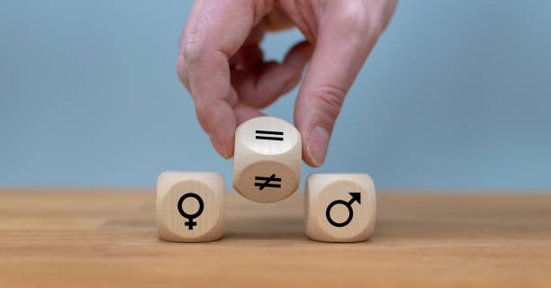 symbol for gender equality. hand turns a dice and changes a unequal sign to a equal sign between symbols of men and women. - gender stereotypes stock pictures, royalty-free photos & images