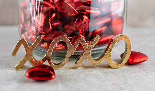 symbol für umarmungen und küsse vor einem glas der herzen. - spenden sammeln stock-fotos und bilder