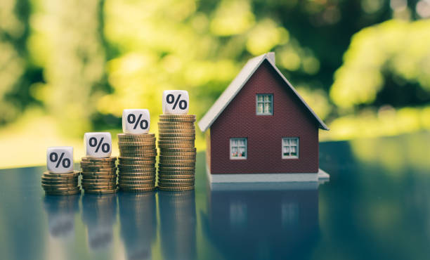 Symbol for increasing interest rates. Dice with percentage symbols on increasing high stacks of coins next to a model house. stock photo