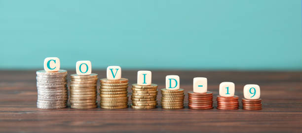 symbol for increasing or reduction expenses due to the corona pandemic. dice form the expression COVID-19 increasing high stack of coins on blue background stock photo