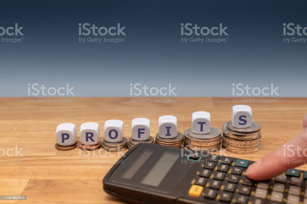 Symbol for increasing profits. Dice placed on stacks of coins form...