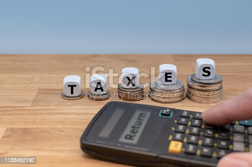 istock Symbol for increasing tax returns. Dice on top of increasing high stacks of coins built the word