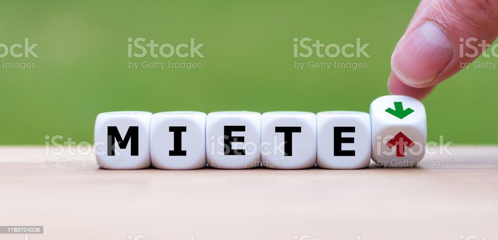 """Symbol für steigende Mieten. Würfel bilden das deutsche Wort """"Miete"""" (""""miete"""" auf Englisch). Eine Hand dreht einen Würfel und ändert die Richtung eines Pfeils. - Lizenzfrei Bauen Stock-Foto"""