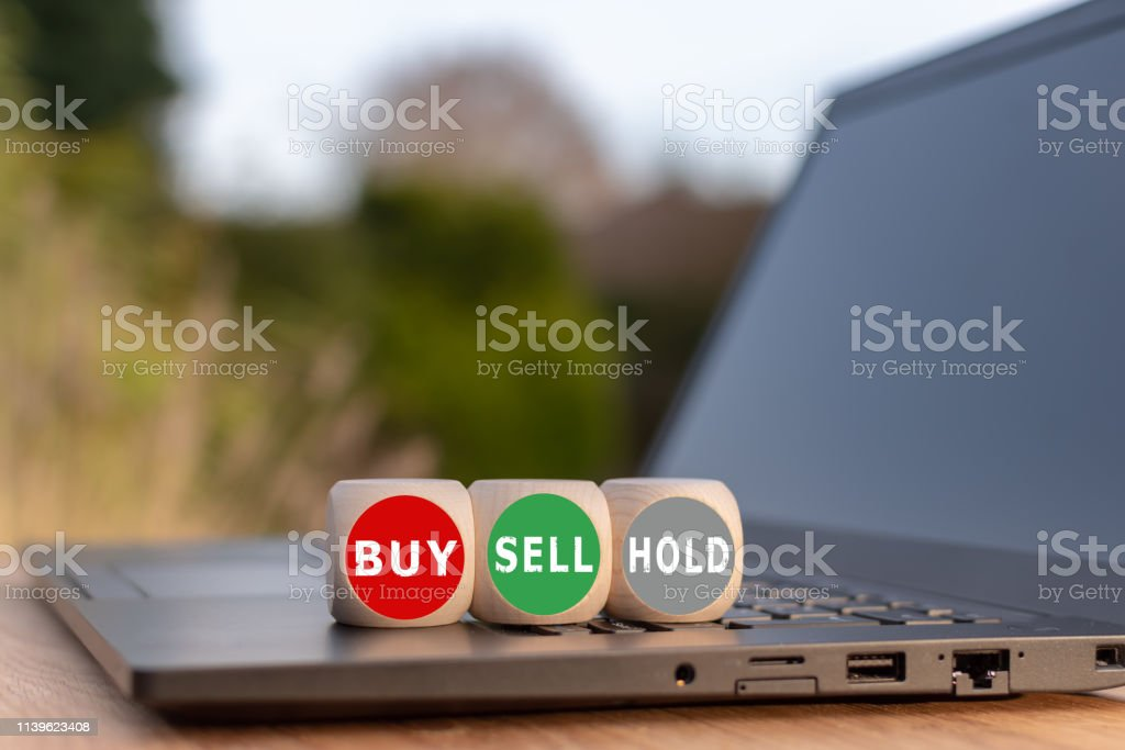 Symbol for the decision to buy, to sell or to hold. Three dice with...