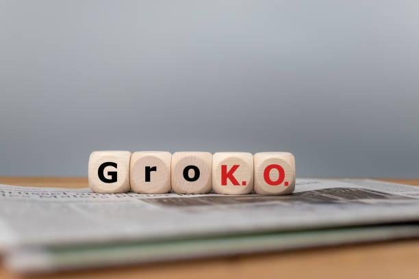 """symbol für das ende der großen koalition namens """"groko"""" zwischen den parteien spd und cdu in deutschland. würfel bilden die abkürzung """"groko"""", die auf einer zeitung steht. - la union stock-fotos und bilder"""