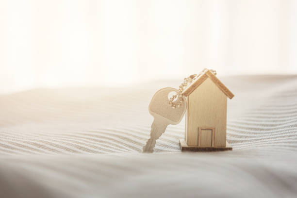 Symbol house with wood key on bed and sunlight. stock photo