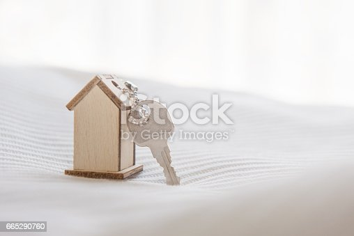 istock Symbol house with wood key on bed and sunlight. 665290760