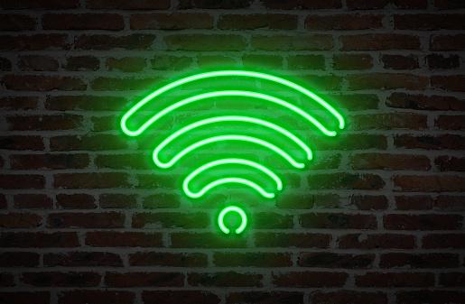 WIFI Symbol Neon Light Sign on Brick Wall Background.