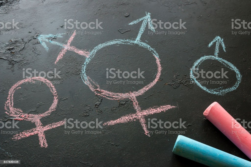 Symbol of a transgender and female and male gender symbols drawn with chalk on a black background stock photo